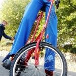 stilt walker on a bicycle