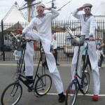 stilt walking sailors on bikes